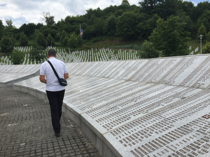 Fikret Ibrakić walks by a list of names commemorating those who died in Srebrenica